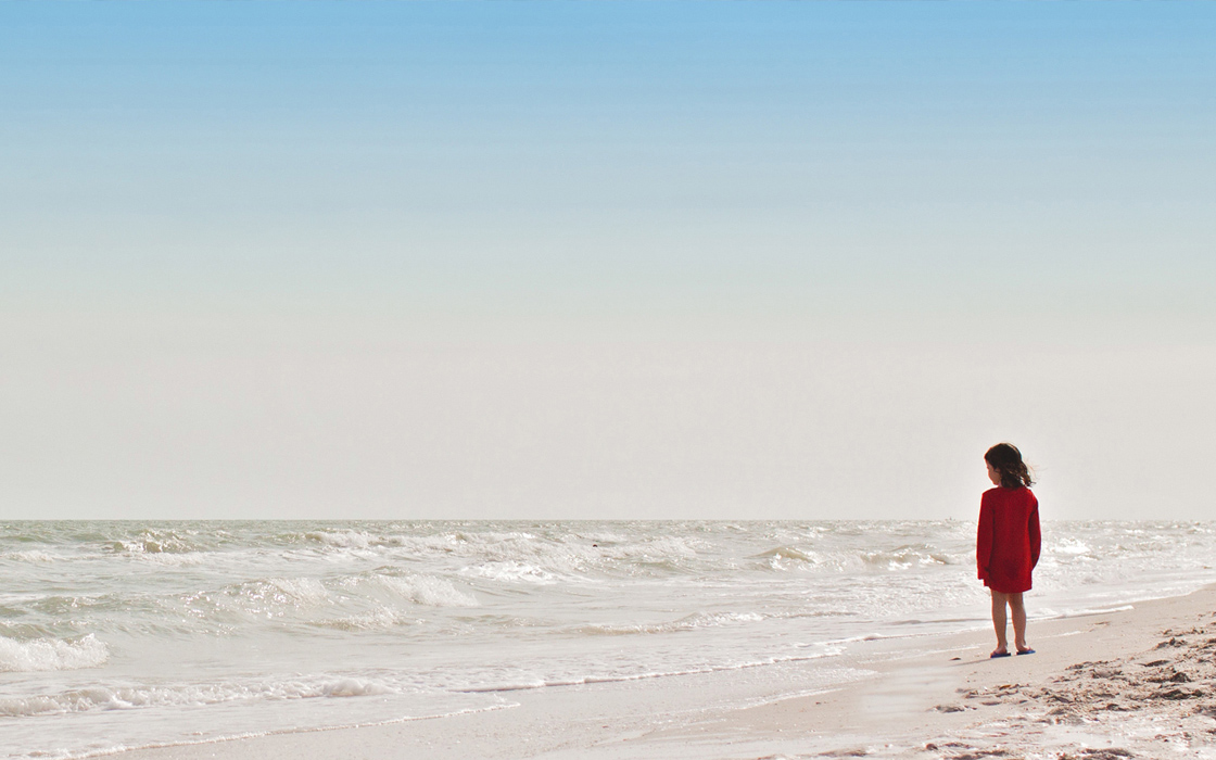 child standing on a beach looking out into the water