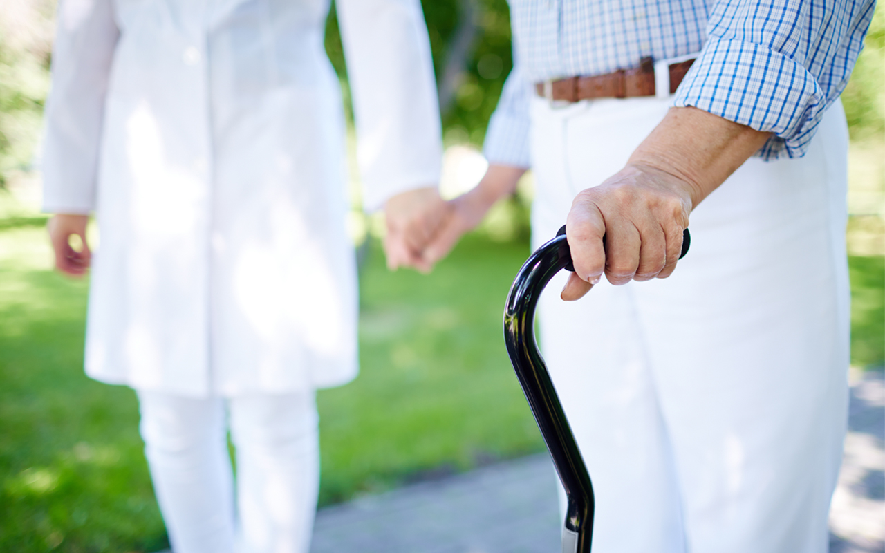 elderly man walking with a cane and holding hands with another