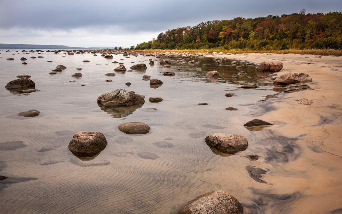 A dark sand shoreline with a close up of the multipe rocks in the shallow water