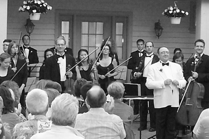 Orchestra performing in front of a seated crowd outside of a home