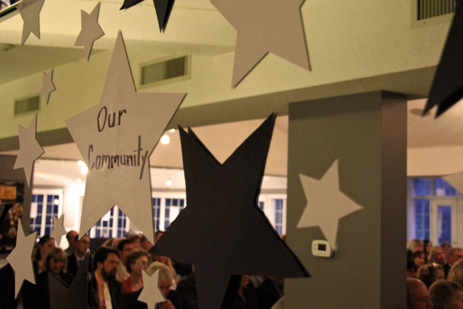 A white star with Our Community written on it hanging from the ceiling at an event with man community members sitting in the background