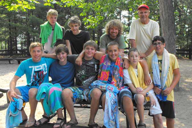 A group of boys (campers) in swimsuits and towels sitting on a picnic table