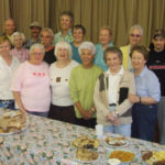 group of people in front of a table of food at the soup kitchen