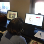 A dark haired woman is sitting in front of a computer