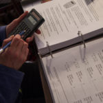 close-up of a person holding a calculator while learning some finance skills