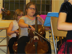 Close up of a young girl playing a base violin