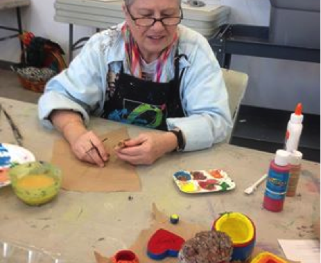 A grey-haired woman wearing glasses sitting at a crafting table