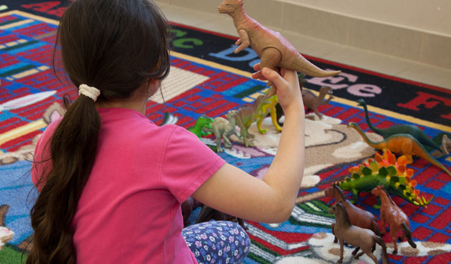 Young girl playing with plastic dinosaurs while sitting on a colourful carpet
