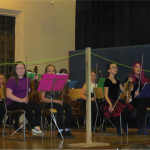 A group shot of young students all playing violins