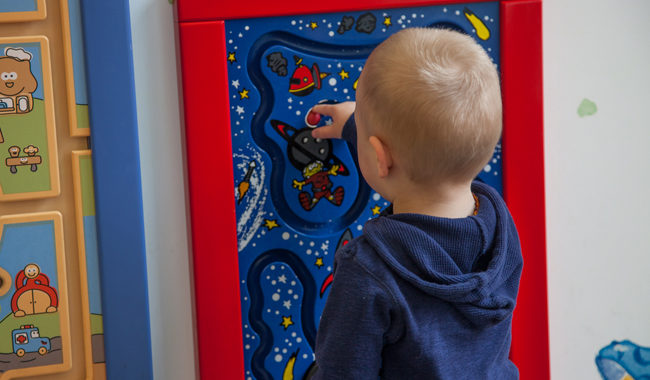 Toddler playing with a board with space pictures on it